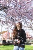 Ragazza con la macchina fotografica che fa le immagini dell'albero di fioritura fotografia stock libera da diritti