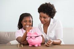 Ragazza con la madre che inserisce le monete nel porcellino salvadanaio immagine stock