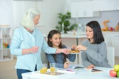 Ragazza con la madre e la nonna che mangiano i creps a casa immagini stock