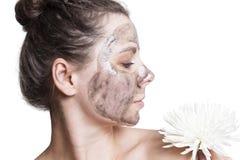 Ragazza con la maschera facciale nera per cura del fronte isolata su fondo bianco Concetto di Skincare immagine stock libera da diritti