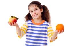 Ragazza con la mela e l'arancio Immagini Stock Libere da Diritti