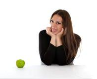 Ragazza con la mela verde che mostra linguetta Fotografia Stock