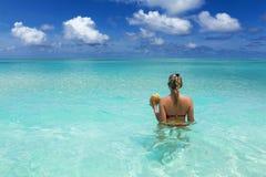 Ragazza con la noce di cocco nell'oceano Fotografia Stock