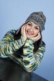 Ragazza con la protezione che sorride alla tabella Immagini Stock Libere da Diritti