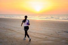 Ragazza con la stuoia di yoga che cammina sulla spiaggia Fotografia Stock Libera da Diritti