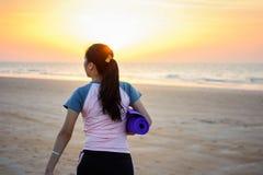 Ragazza con la stuoia di yoga sulla spiaggia Fotografia Stock Libera da Diritti