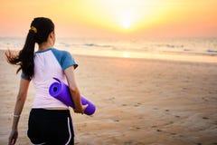 Ragazza con la stuoia di yoga sulla spiaggia Immagini Stock