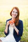 Ragazza con la tazza arancio Fotografia Stock