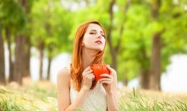 Ragazza con la tazza arancio Fotografia Stock Libera da Diritti