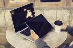Ragazza con la tazza di caffè di carta, la compressa digitale ed il computer portatile all'aperto Fotografia Stock Libera da Diritti