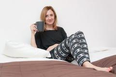 Ragazza con la tazza a letto Immagini Stock