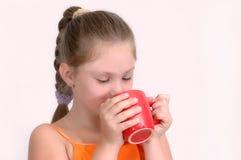 Ragazza con la tazza rossa Immagini Stock