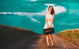 Ragazza con la valigia alla strada rurale immagine stock libera da diritti
