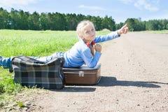 Ragazza con la valigia che sta circa la strada fotografia stock libera da diritti