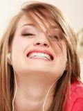 Ragazza con le cuffie bianche che ascolta la musica Immagini Stock