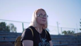 Ragazza con le cuffie che ascolta la musica e che si siede sul podio dello stadio che balla alla musica Bei colpi freschi archivi video
