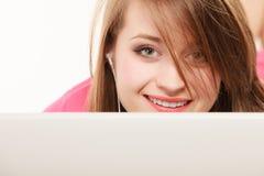 Ragazza con le cuffie ed il computer portatile che ascolta la musica Immagine Stock Libera da Diritti