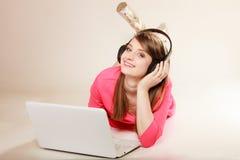 Ragazza con le cuffie ed il computer portatile che ascolta la musica Immagini Stock