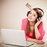 Ragazza con le cuffie ed il computer portatile che ascolta la musica Immagini Stock Libere da Diritti