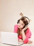 Ragazza con le cuffie ed il computer portatile che ascolta la musica Fotografia Stock