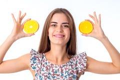 Ragazza con le fette arancio in mani Immagine Stock
