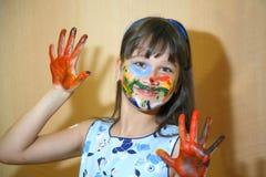 Ragazza con le mani verniciate Ritratto di un bambino macchiato con le pitture Fotografie Stock