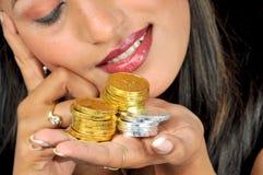 Ragazza con le monete dorate e d'argento fotografia stock