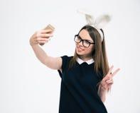 Ragazza con le orecchie del coniglietto che fanno la foto del selfie sullo smartphone Fotografia Stock