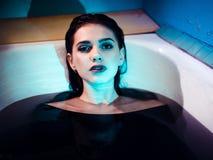 Ragazza con le spalle nude che si trovano nel bagno con acqua porpora colorata Concetto di modo fotografie stock