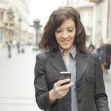 Ragazza con lo smartphone che cammina sulla città Fotografia Stock