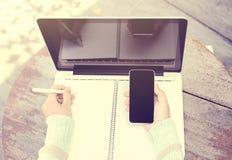 Ragazza con lo smartphone, il diario in bianco con la penna ed il computer portatile su un woode Fotografia Stock
