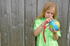 Ragazza con lo stetoscopio sul globo del mondo Fotografie Stock Libere da Diritti