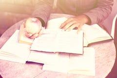 Ragazza con molti libri aperti e la mela sulla tavola, foto del instagam Immagine Stock