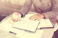 Ragazza con molti libri aperti su una tavola Immagine Stock