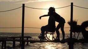Ragazza con osservare handicappato felice nell'orizzonte su fondo del tramonto l'acqua eccessiva il viaggio di estate video d archivio
