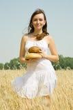 Ragazza con pane al giacimento dei cereali Fotografie Stock Libere da Diritti