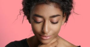 Ragazza con pelle marrone chiaro perfetta e bei capelli neri ricci che sorride alla macchina fotografica Fotografie Stock