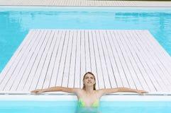 Ragazza con prendere il sole chiuso degli occhi al Poolside immagine stock libera da diritti