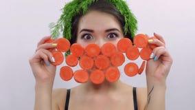 Ragazza con prezzemolo verde sulla testa, fronte della copertura dai cerchi della carota ballo Sorriso video d archivio