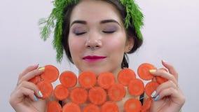 Ragazza con prezzemolo verde sulla testa, fronte della copertura dai cerchi della carota proposta Sorriso video d archivio