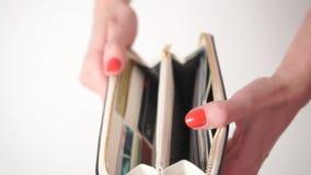 Ragazza con smalto rosso che apre la sua borsa bianca con le carte di credito stock footage