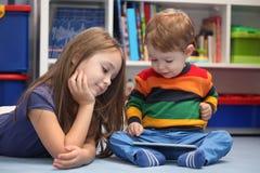 Ragazza con suo fratello piccolo che per mezzo di un computer digitale della compressa Immagine Stock