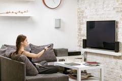 Ragazza con telecomando a disposizione, sedendosi su un sofà e su un wa Fotografie Stock