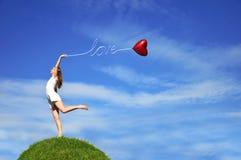 Ragazza con un aerostato rosso sotto forma di cuore Fotografia Stock Libera da Diritti