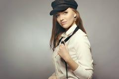 Ragazza con un berretto nero su un fondo grigio fotografie stock