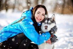 Ragazza con un cane nel husky di inverno Fotografia Stock