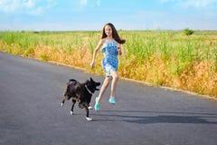 Ragazza con un cane per una passeggiata Fotografia Stock