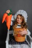 Ragazza con un canestro e carote su un fondo grigio Immagini Stock