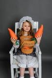 Ragazza con un canestro e carote su un fondo grigio Fotografia Stock