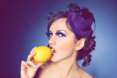 Ragazza con un cappello e un limone viola nella bocca Immagini Stock Libere da Diritti